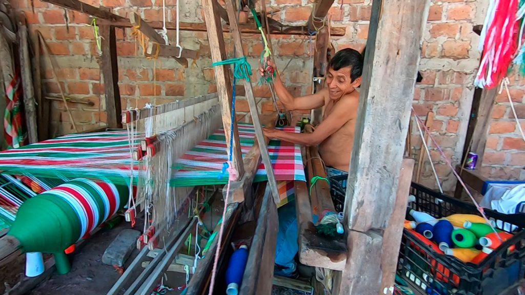 Poblador de San Sebastian trabajando en un telar artesanal